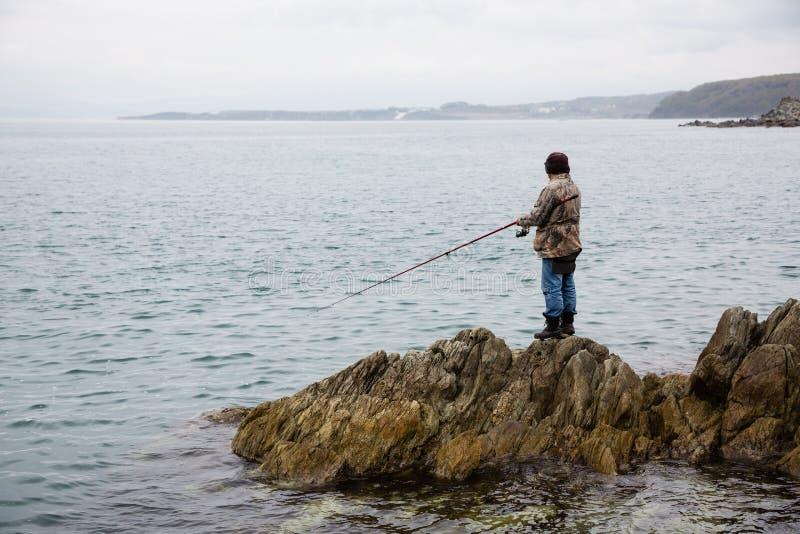 渔民在礁石上钓鱼 免版税图库摄影