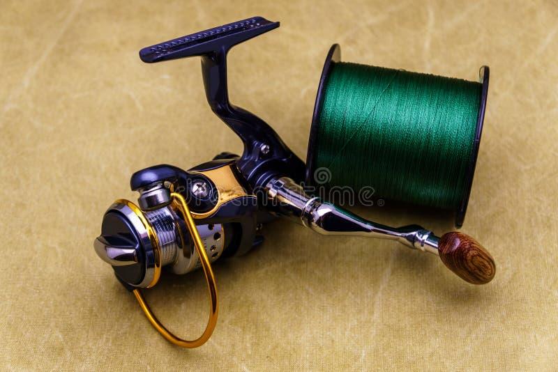 渔绳子卷轴和短管轴在篷布背景的  钓鱼绿线 渔结辨的钓丝卷轴和短管轴  库存图片