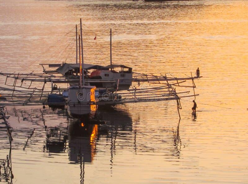 渔船和渔夫,现出轮廓反对黄色/橙色海,弗洛勒斯,印度尼西亚,亚洲 免版税库存照片