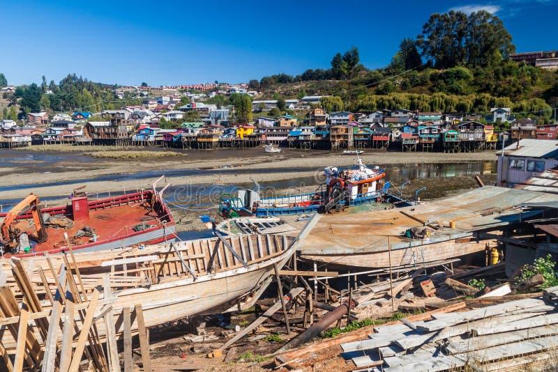 渔船和palafitos高跷房子在低潮期间在卡斯特罗,奇洛埃岛海岛,池氏 图库摄影