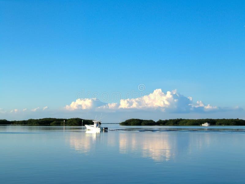 渔船在水在有土地的佛罗里达群岛在非常蓝色海洋和巨大的蓬松云彩的反映的距离- 免版税图库摄影