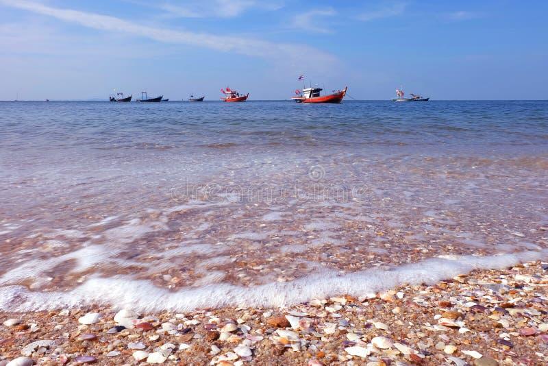 渔船说谎在船锚由海和海滩和五颜六色的壳 图库摄影