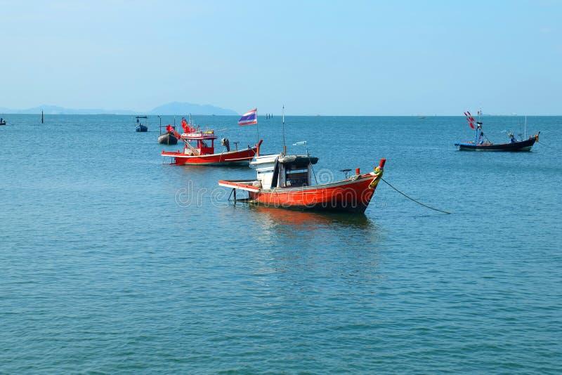 渔船说谎在船锚由海和海滩和五颜六色的壳 免版税库存图片