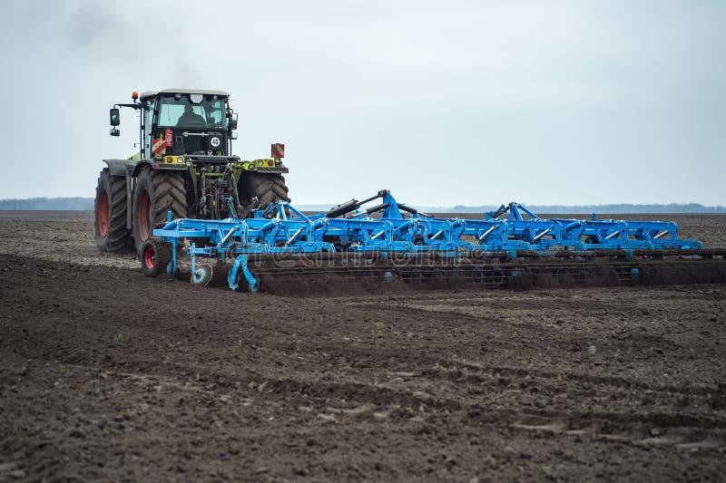 温床耕地机和土地耕种与拖拉机 免版税图库摄影