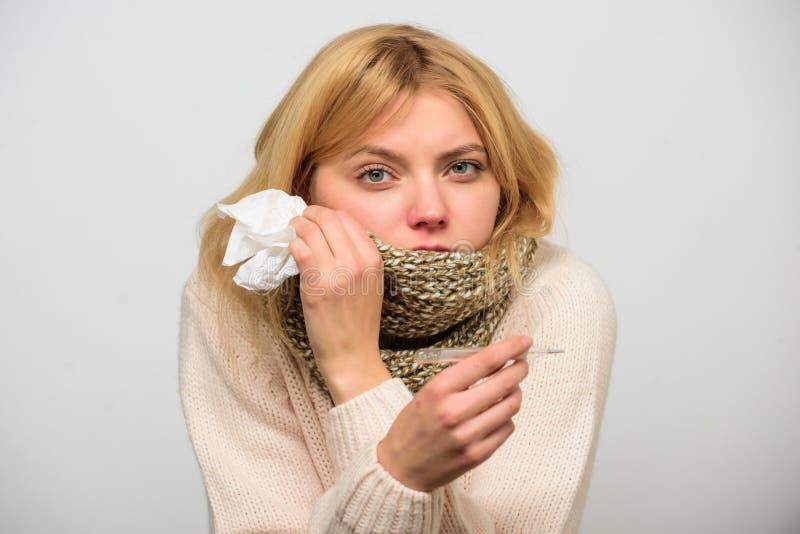 温度流感症状 由于热病,妇女非常感觉 需要热病的疗程 围巾举行温度计的女孩 图库摄影