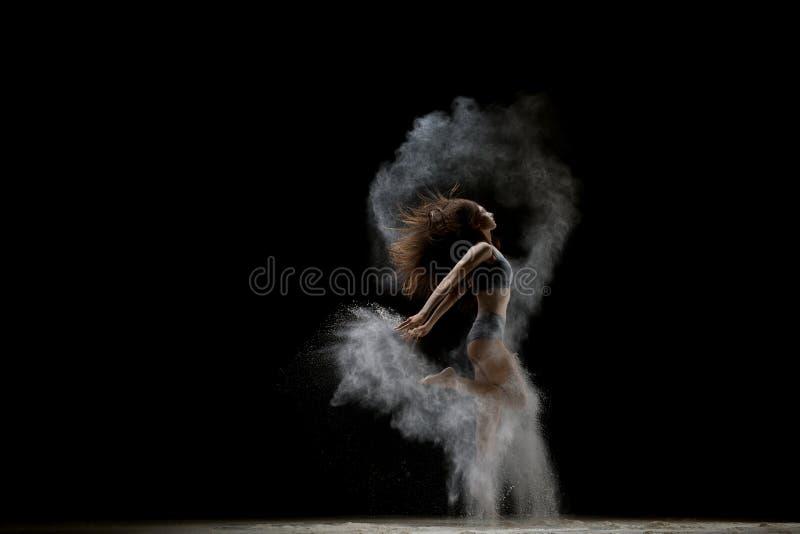温文地跳在白色尘云射击的女孩 库存图片