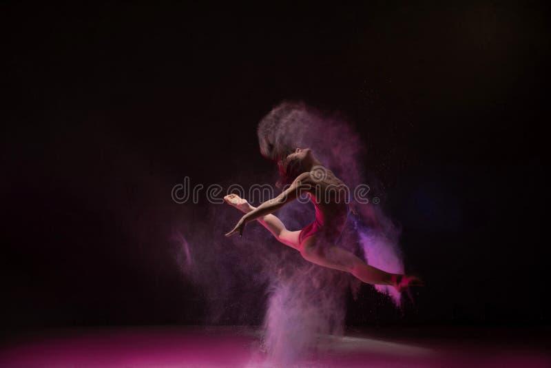 温文地跳在颜色尘云的妇女 库存照片