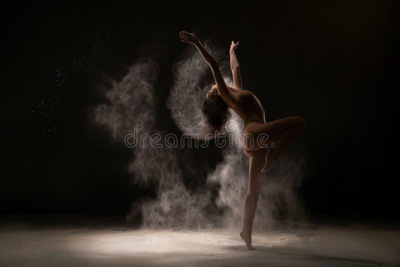 温文地跳舞在白色尘云的体操运动员 免版税库存图片