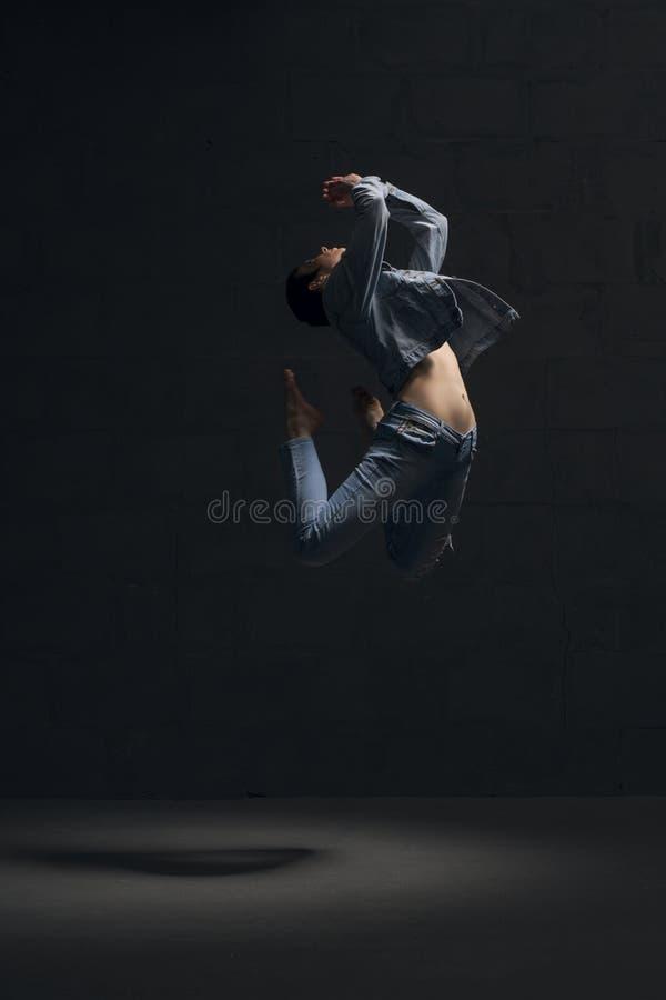 温文地跳舞在黑暗的jeanswear的女孩 库存图片