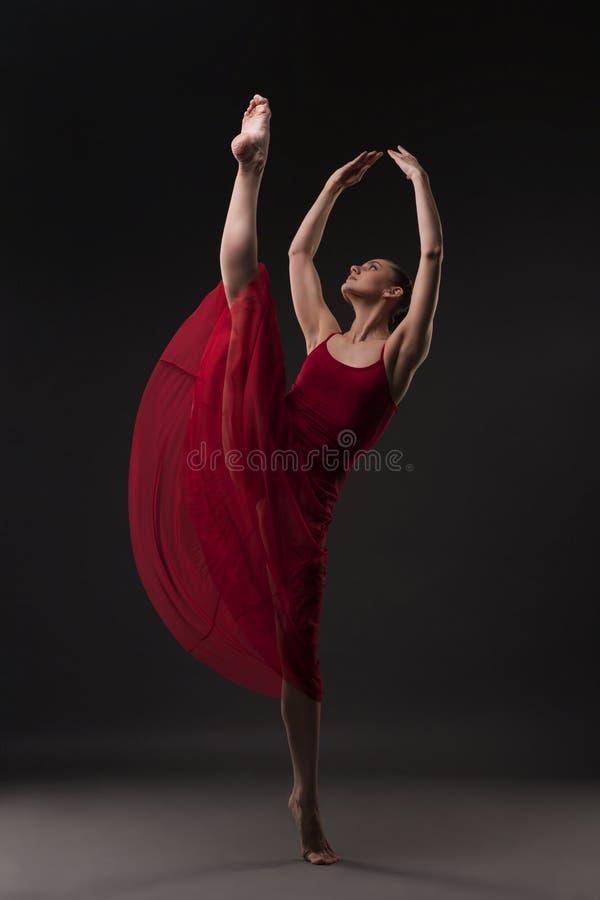 温文地跳舞红色的礼服的美丽的女孩 免版税图库摄影
