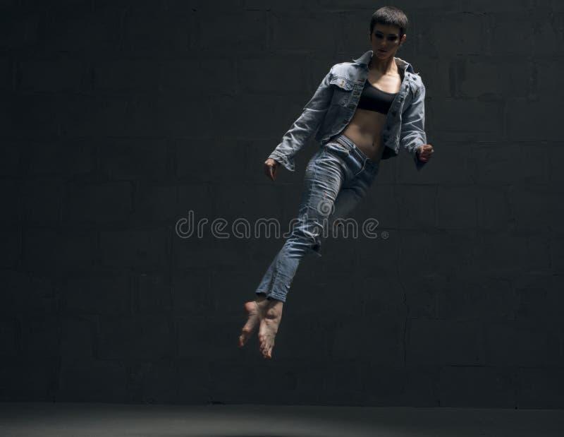 温文地跳跃在黑暗的jeanswear的女孩 免版税库存图片