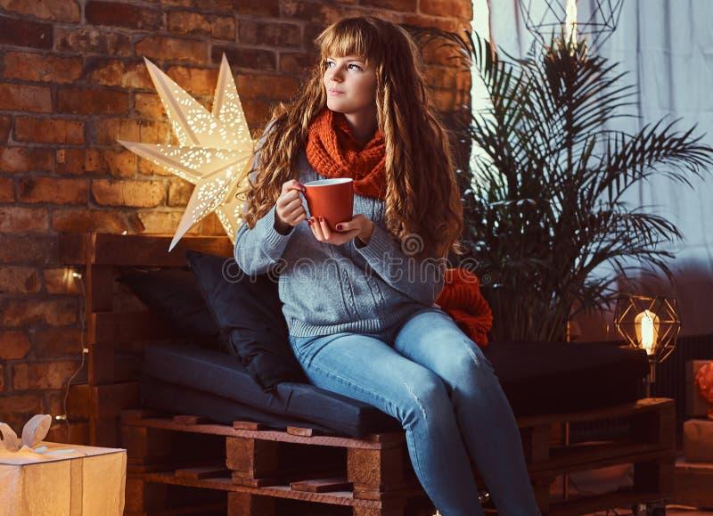 温暖与一杯咖啡的红头发人女孩在一个装饰的客厅在圣诞节打过工 图库摄影