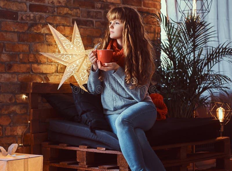 温暖与一杯咖啡的红头发人女孩在一个装饰的客厅在圣诞节打过工 免版税图库摄影