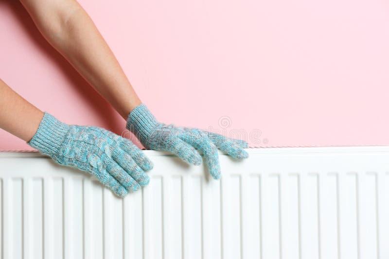 温暖在热化幅射器的手套的妇女手在颜色墙壁附近 免版税库存图片