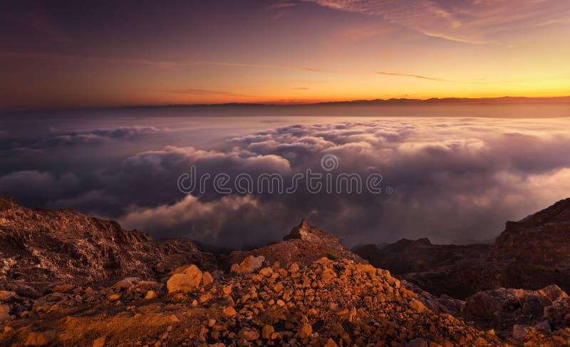温暖在Hafeet山的发光的日出在云彩上 图库摄影