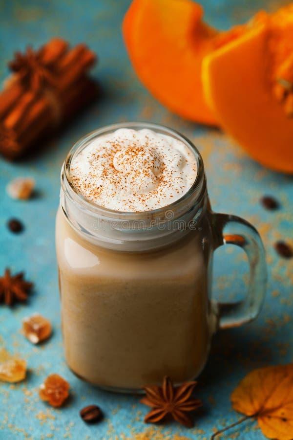 温暖的南瓜加了香料拿铁或在杯子的咖啡装饰了桂香和茴香在蓝色葡萄酒背景 秋天,秋天,冬天热的饮料 免版税库存照片