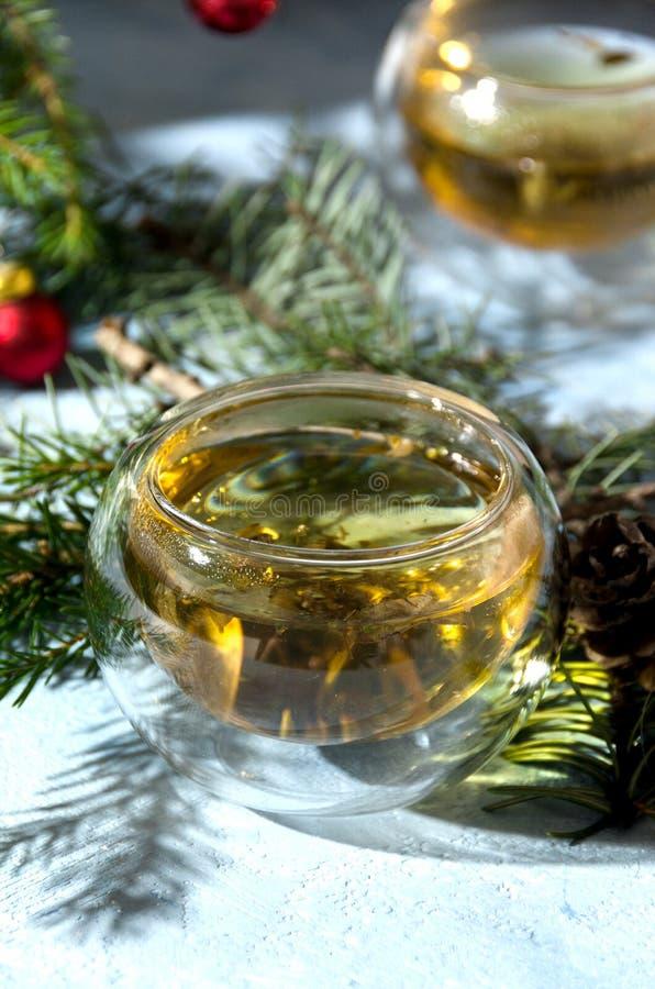 温暖的圣诞节茶玻璃杯子杉木锥体 库存图片