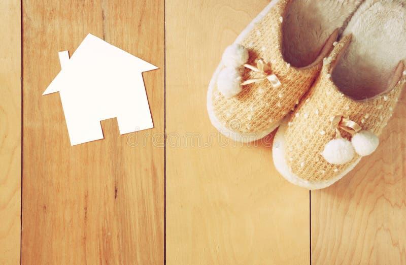 温暖的妇女拖鞋顶视图在木地板和纸房子形状的作为受欢迎的家庭概念 库存照片
