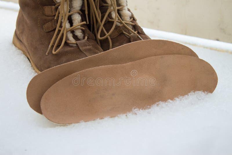 温暖的棕色鞋子和矫形皮鞋的内底 冬天背景,脚 库存图片