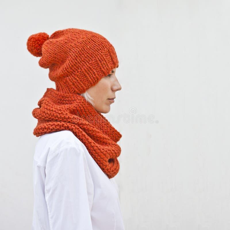 温暖的橙色被编织的帽子和妇女发网的俏丽的年轻女人 图库摄影