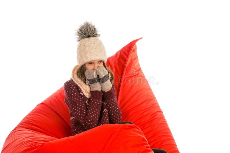 温暖的毛线衣、帽子、围巾和手套的女孩坐红豆 库存照片