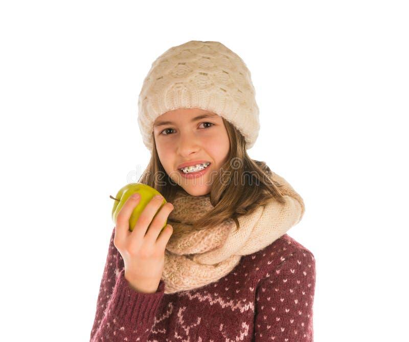温暖的毛线衣、帽子、围巾和手套的微笑的女孩吃a的 库存照片