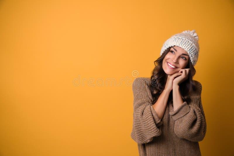 温暖的毛线衣和帽子的年轻女人在黄色背景 圣诞节季节 免版税图库摄影
