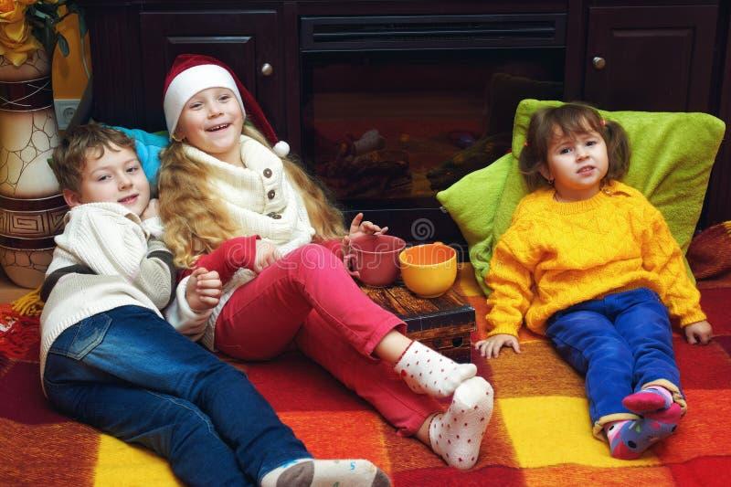 温暖的毛线衣的快乐的孩子由壁炉 图库摄影