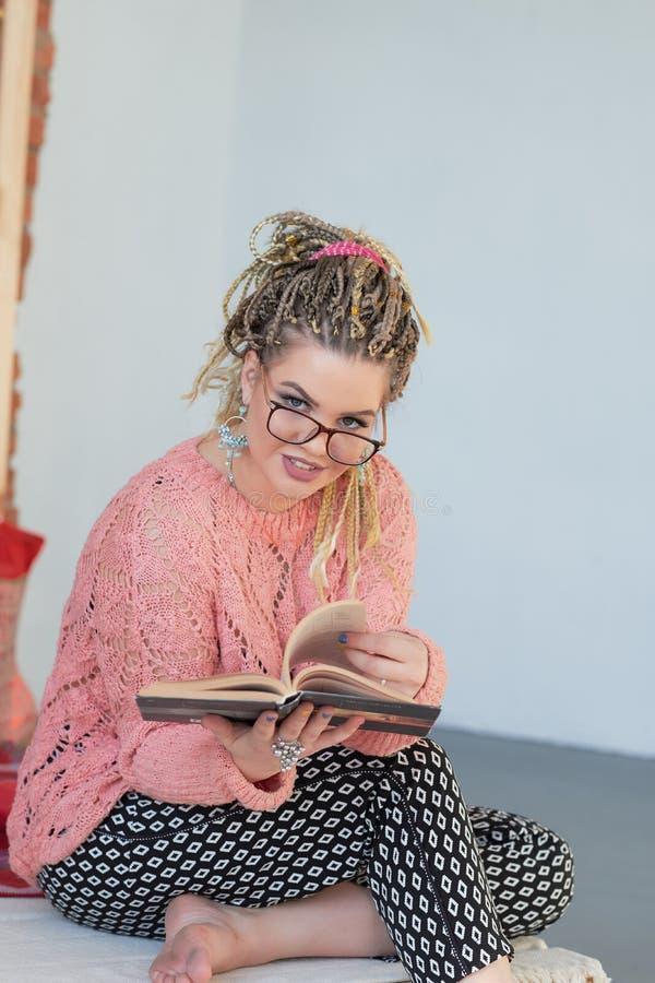 温暖的毛线衣看书的年轻美女在床上在家 免版税库存照片