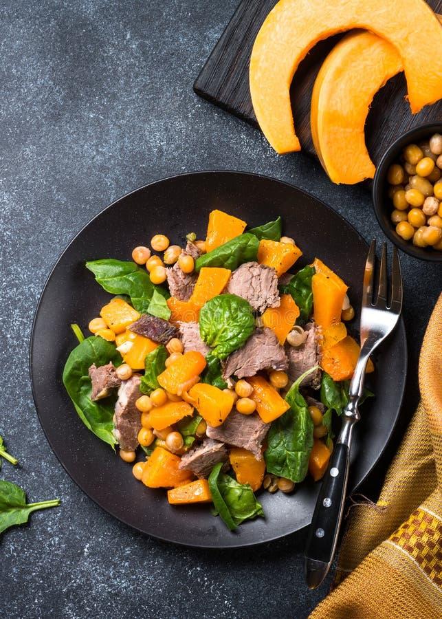 温暖的沙拉用南瓜、被烘烤的牛肉、菠菜和鸡豆 免版税库存图片