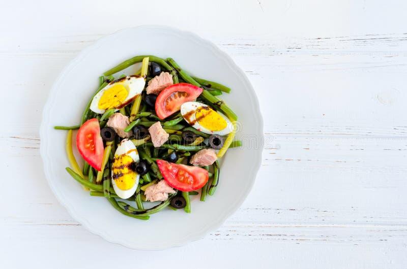 温暖的沙拉用青豆、金枪鱼、蕃茄和煮沸的鸡蛋 免版税库存图片