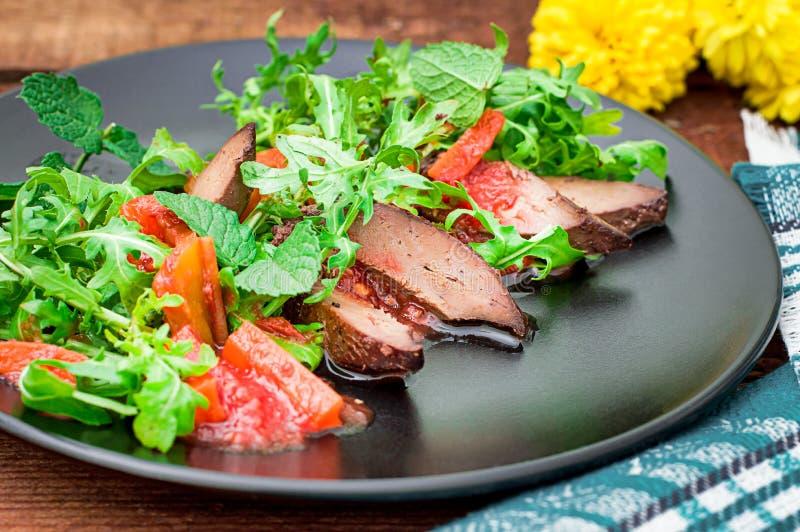 温暖的沙拉,与芝麻菜,鲜美,时兴的食物,新的盘服务的鸭子 背景土气木 顶视图 免版税库存照片