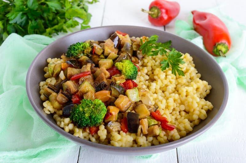 温暖的素食主义者沙拉用蒸丸子和油煎的菜茄子,夏南瓜,葱,甜椒,硬花甘蓝 库存照片