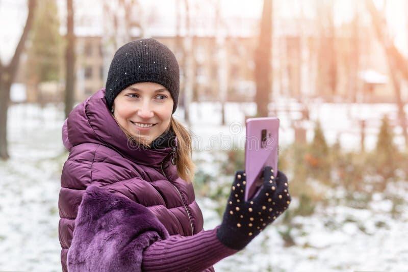 温暖的紫色黎明夹克的微笑年轻愉快的妇女,当做与智能手机的selfie在步行期间在冬天城市公园时 相当 免版税库存照片