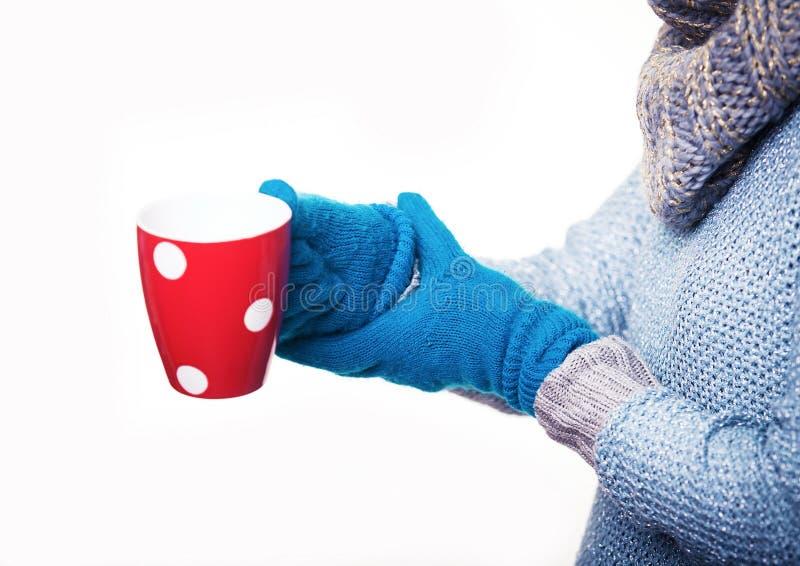 温暖的红色杯子茶 拿着杯子蓝色手套的女孩 图库摄影