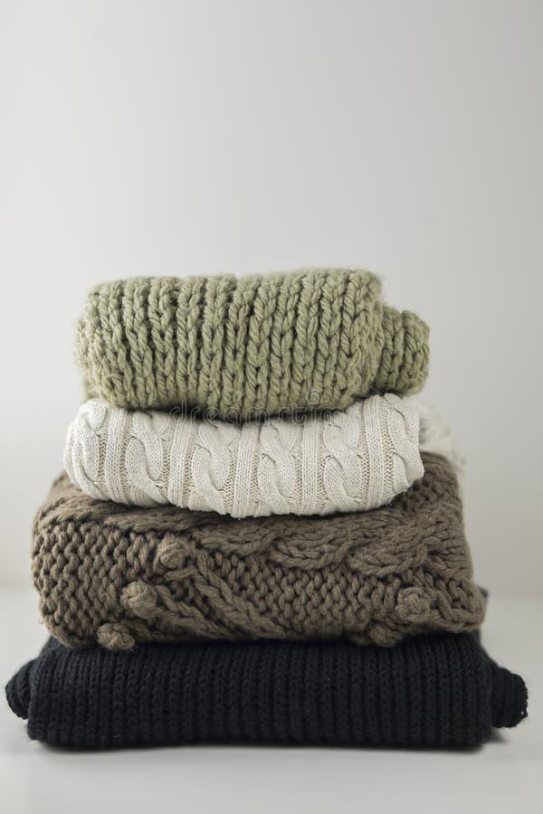 温暖的羊毛被编织的冬天和秋天衣裳,折叠在一张白色桌上的堆 毛线衣,围巾 安置文本 免版税库存图片