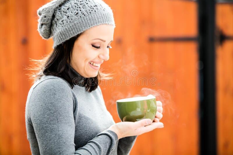 温暖的衣裳和灰色帽子的美丽的绿眼的少妇 免版税库存照片