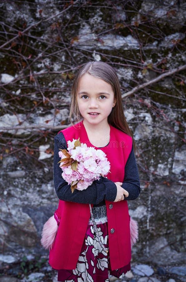 温暖的衣裳的一个小女孩拿着花花束 免版税库存照片