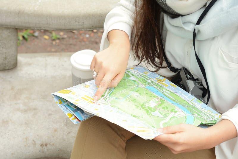 温暖的衣裳的年轻体贴的旅游女孩有地图的 库存照片