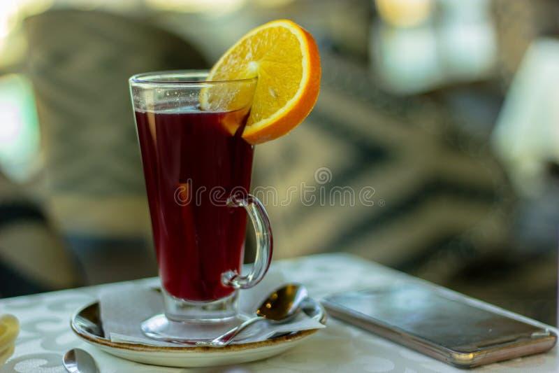 温暖饮料用在板材和电话的一个桔子 免版税库存照片
