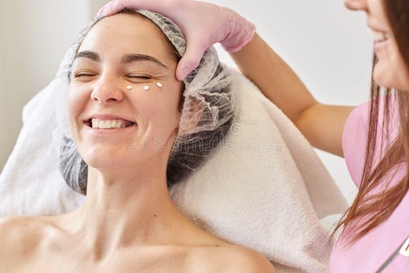 温泉、秀丽、皮肤和身体关心概念 年轻女人,可及面部秀丽治疗的整容术诊所的客户温泉沙龙 免版税库存图片