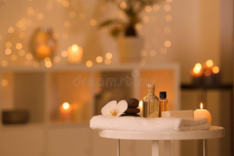 温泉供应、燃烧的蜡烛和花在桌上在发廊 图库摄影