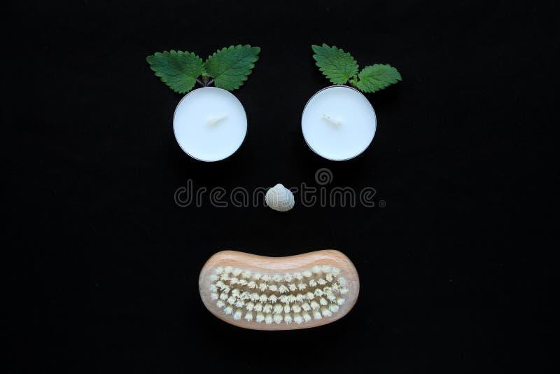 温泉健康概念、面孔与眼睛蜡烛,贝壳鼻子和一把木身体刷子的嘴在黑背景 库存图片