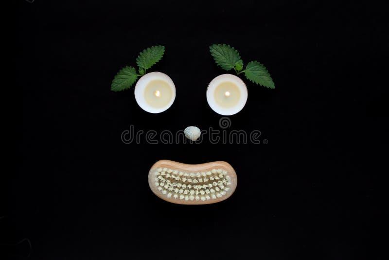 温泉健康概念、面孔与眼睛蜡烛,贝壳鼻子和一把木身体刷子的嘴在黑背景 图库摄影