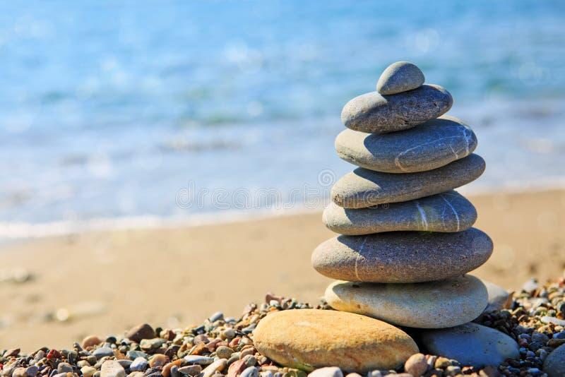 温泉向在海滩的平衡扔石头 免版税库存图片