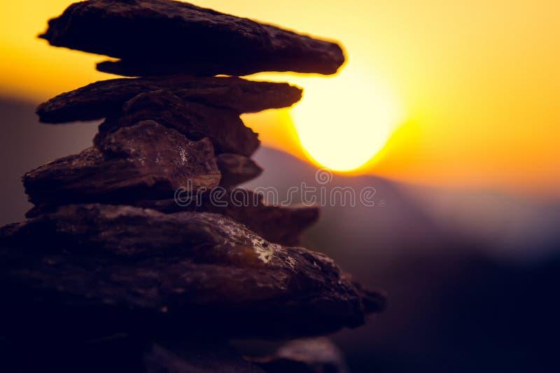 温泉向平衡、五颜六色的夏天天空被堆积的小卵石背景、剪影和蝴蝶,美好的自然扔石头 免版税库存照片