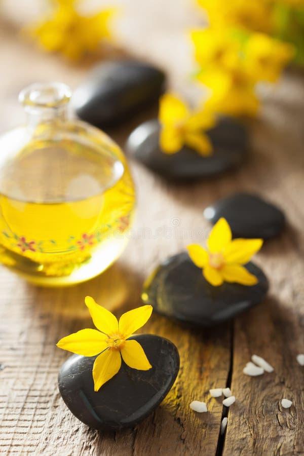 温泉向精油和黄色花扔石头温泉的 免版税库存图片