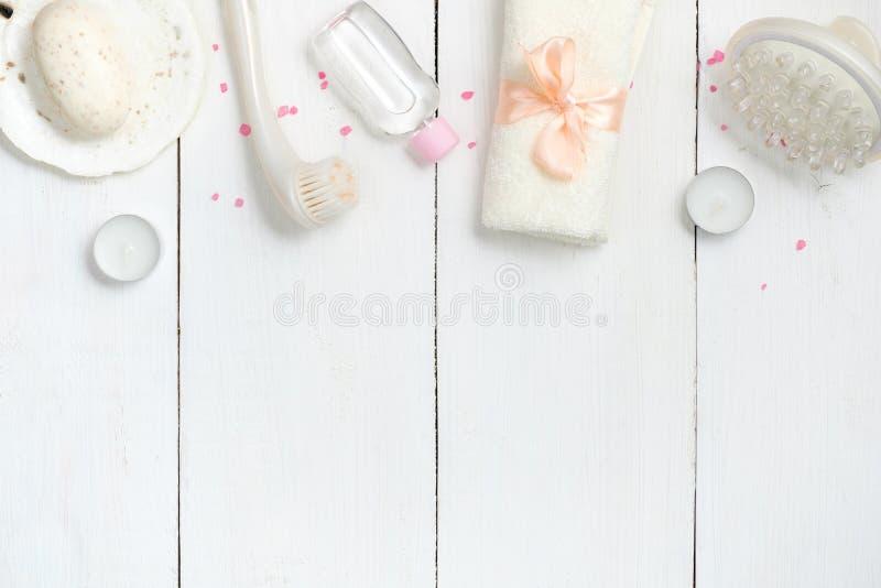 温泉在白色木桌上的秀丽化妆用品框架或边界从上面 平的被放置的构成,顶视图,在头顶上 免版税库存照片