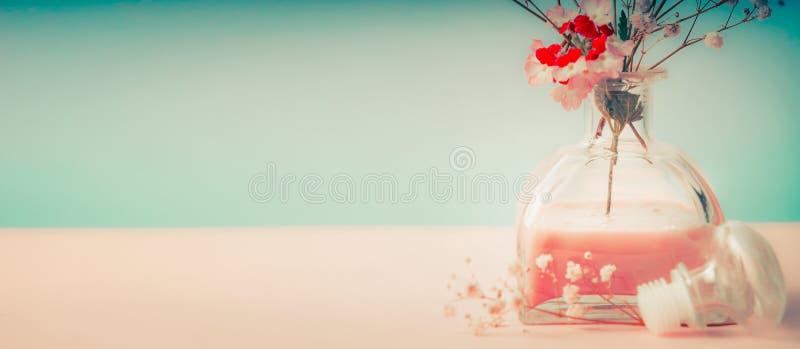 温泉或健康背景与室芬芳瓶和花在淡色背景,正面图 库存照片