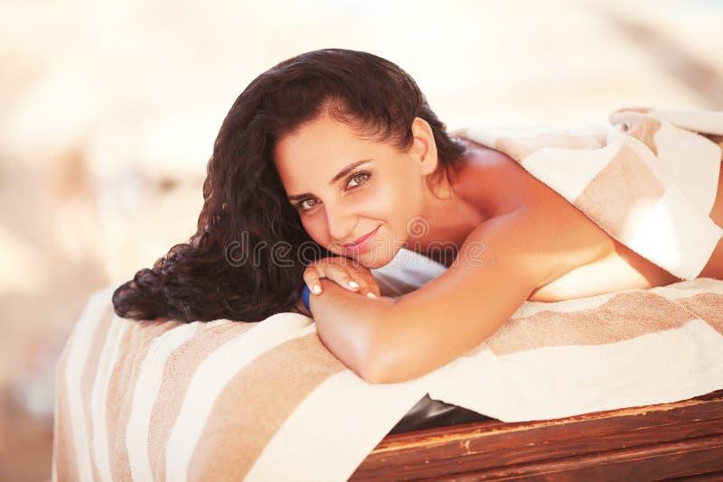 温泉按摩 接受后面按摩的轻松的微笑的妇女 免版税库存照片